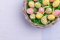 Top view of Easter quail eggs and feathers in a wicker basket, close-up. Easter greetings card. Stock Photography