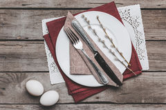 Top view of Easter table setting with cutlery, catkins and Easter eggs on wooden table Royalty Free Stock Photos