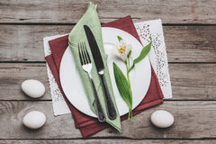 Top view of Easter table setting with cutlery, spring flower and Easter eggs on wooden table Royalty Free Stock Photos