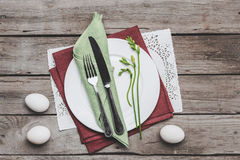 Top view of Easter table setting with cutlery, spring plant and Easter eggs on wooden table Stock Photos