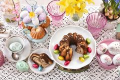 Top view of easter traditional cakes on festive table. Easter traditional marble ring cake partly sliced and cupcakes with beautiful decorations  on festive Stock Photos