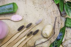 Top view eco friendly natural bamboo toothbrush place on wooden plates and toothpaste made from salt,charcoal and Aloe,concept royalty free stock images