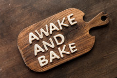 Top view of edible lettering awake and bake made from dough on wooden cutting board. Baking cookies concept Royalty Free Stock Images