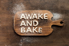 Top view of edible lettering awake and bake made from dough on wooden cutting board. Baking cookies concept Royalty Free Stock Photography