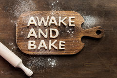 Top view of edible lettering awake and bake made from dough on wooden cutting board. Baking cookies concept Stock Image