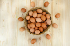 Top View of eggs put in a wicker basket in wooden background. Full of Eggs decorated in a wicker basket in wooden background from top view Royalty Free Stock Image