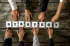 Top view of eight business people assembling the word STRATEGY. While each holding one card with letter on it. Conceptual of cooperation in finding the best Royalty Free Stock Photography