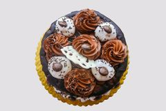 Top view of an elaborate chocolate cake with chocolate swirls and whipped cream poofs and chocolate sprinkles. A Top view of an elaborate chocolate cake with Stock Photos