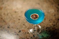 Top view of elegant glass with fresh and sweet summer cocktail with blue liquor and slice of orange. Top view of elegant glass with fresh and sweet summer Stock Photography