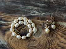 Top view on Elegant set of pearl braclet and earrings on wooden background. Close up Stock Images