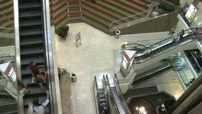Top view of elevators and escalators moving within mall (1 of 2). A view or scene of Shopping stock video footage