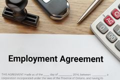 Top view of Employment agreement lay down on wooden desk with ru. Bber stamp and calculator Royalty Free Stock Images