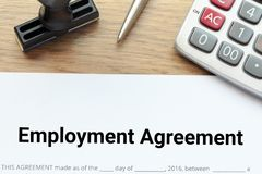 Top view of Employment agreement lay down on wooden desk with ru. Bber stamp and calculator Royalty Free Stock Photography
