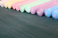 Top view of empty blackboard with colorful chalks Royalty Free Stock Images