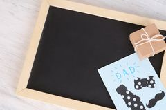 Top view empty blackboard with greeting card and gift box. On wooden backround. Father`s day concept Stock Images