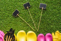 Top view of empty blackboards, rubber boots, protective gloves, flower pot. And gardening tools stock photography