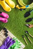 Top view of empty blackboards, rubber boots, protective gloves and gardening equipment. On grass stock photos