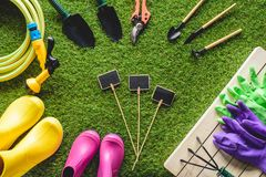 Top view of empty blackboards surrounded by rubber boots, gardening equipment and protective gloves. On grass royalty free stock photography