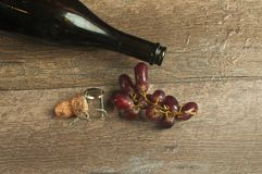 Top view of an empty bottle of french champaign with cork and grapes. Top view, close up of the neck of an empty bottle of french champaign with the cork stock images