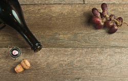 Top view of empty bottle of champaign with cork and grapes. Top view of empty bottle neck of champaign with cork, wire retaining cap and freshly picked red Stock Photography