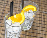 Top of view of empty cocktail glasses with two orange slices and ice cubes. On wood table Stock Photo