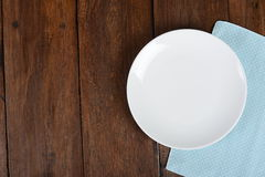Top View Empty Dish On The Table Background. Empty plate, old fork and knife on wooden background Royalty Free Stock Image