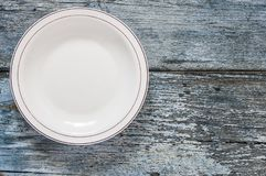 Top view empty dish on wooden background. Empty plate on blue wooden background. Top view with copy space royalty free stock photography