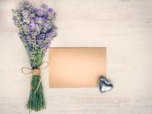 Top view of an empty greeting kraft card, lavender bouquet and silver heart over white wood rustic wooden table. Kraft mockup. Top view of an empty greeting Royalty Free Stock Image