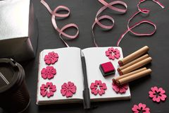 Top view of an empty notebook, scrapbook accessories and a cup of coffee on a black background. Top view of an empty notepad, scrapbook accessories, pink stock photo