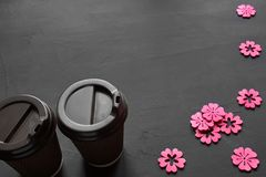 Top view of an empty notebook, scrapbook accessories and a cup of coffee on a black background. Top view of two cups of tea and pink scrapbook stencils on a royalty free stock photo