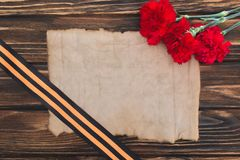 Top view of empty old paper, carnations and st. george ribbon on wooden surface royalty free stock image