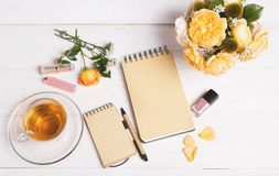 top view of empty open notebook with pen, flowers English rose, cosmetics and cup of tea on table top Royalty Free Stock Photos
