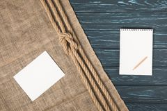 Top view of empty paper on sackcloth with knotted rope and blank textbook with pencil royalty free stock images