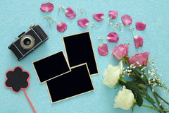 Top view of empty photo frames next to old camera and roses Royalty Free Stock Photography