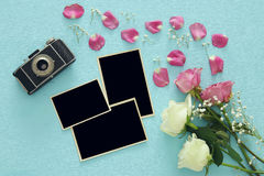 Top view of empty photo frames next to old camera and roses Royalty Free Stock Images