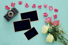 Top view of empty photo frames next to old camera and roses Stock Photo