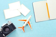 Top view of empty photographs frame next to airplane, camera and blank notebook over wooden table. traveling concept. ready to royalty free stock photos