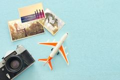 Top view of empty photographs next to airplane and camera over wooden table. traveling concept. ready to mock up stock photo
