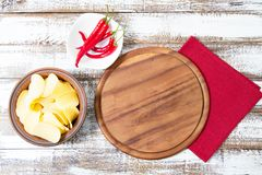 Top view - empty pizza desk board on wood table with chili pepper and potato chips, mock up royalty free stock photos