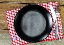 Top view of empty plate with spoon and knife placed on Royalty Free Stock Photos