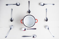 Top view of empty pot with spoons on symmetry Royalty Free Stock Photography