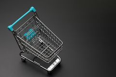 Top view of empty shopping cart with blue handle on dark black b. Ackground with copy space Stock Photography