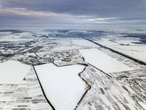 Top view of empty snowy fields on winter morning on dramatic cloudy sky background. Aerial drone photography concept.  royalty free stock image