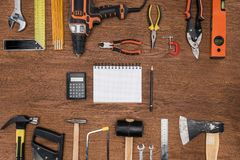 Top view of empty textbook calculator and pencil surrounded by arranged various tools. On wooden table royalty free stock images