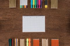 Top view of empty textbook near arranged various pencils and markers on wooden. Table royalty free stock photos