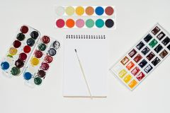 Top view of empty textbook and paintbrush surrounded by colorful paints. On white table stock photography