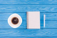 Top view of empty textbook, pen and coffee cup on blue. Wooden planks royalty free stock photo