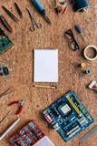 Top view of empty textbook and pen with repairing tools and motherboard. On wooden table royalty free stock photo