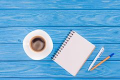 Top view of empty textbook, pens and cup of coffee on blue. Wooden planks stock photos