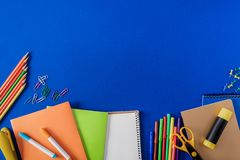 Top view of empty textbook and variety stationery on blue. Background royalty free stock photos